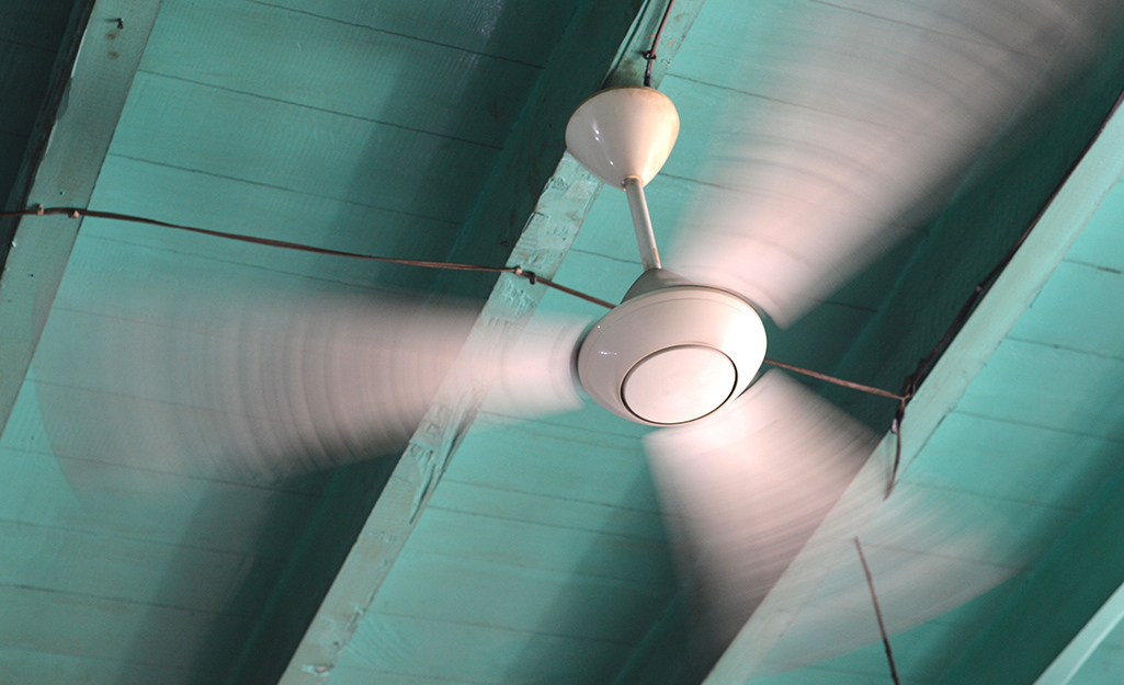 A white ceiling fan spinning under a green ceiling.