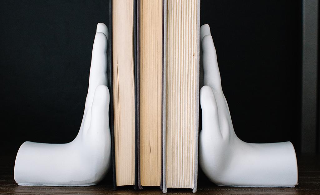 Hai quả cầu bằng gốm hình bàn tay thích hợp giữ thẳng đứng ba cuốn sách.