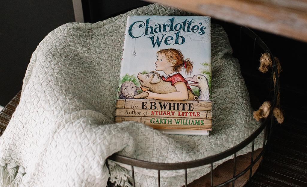 Một cuốn sách nằm trên một chiếc chăn trong một giỏ dây trên giá sách.