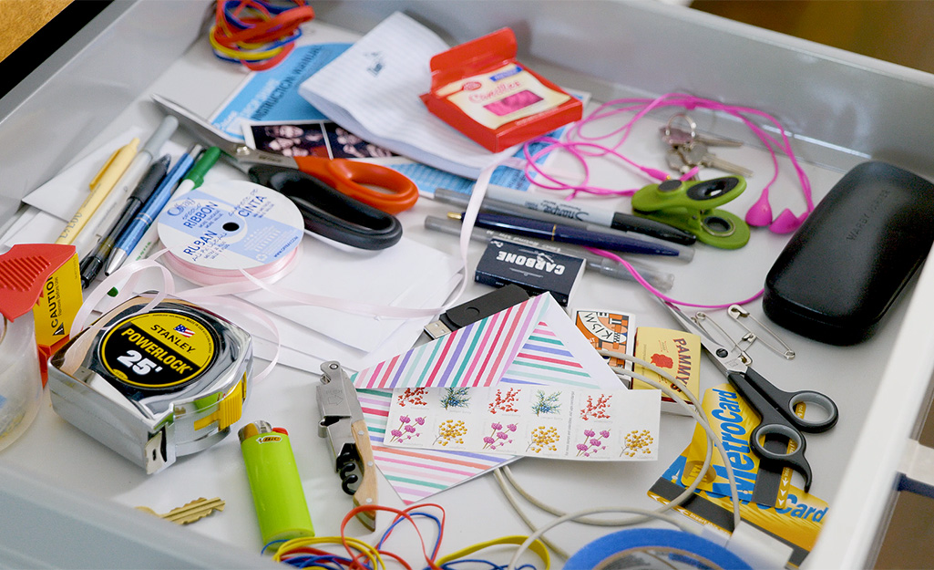 A messy drawer holds glasses, scissors and more.