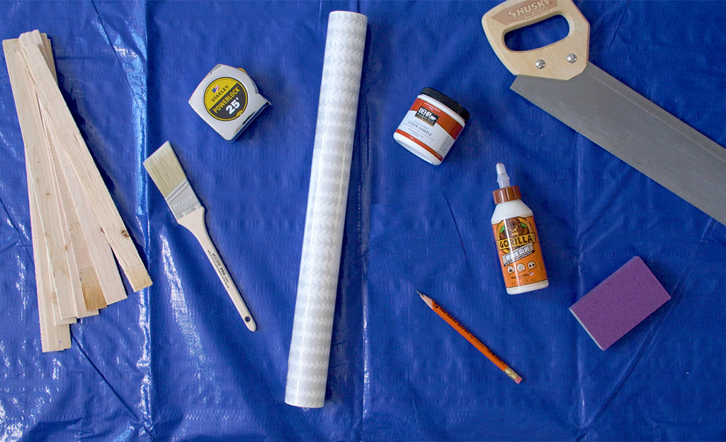 Wood shims, tape measure, a saw and other supplies lay on a tarp.