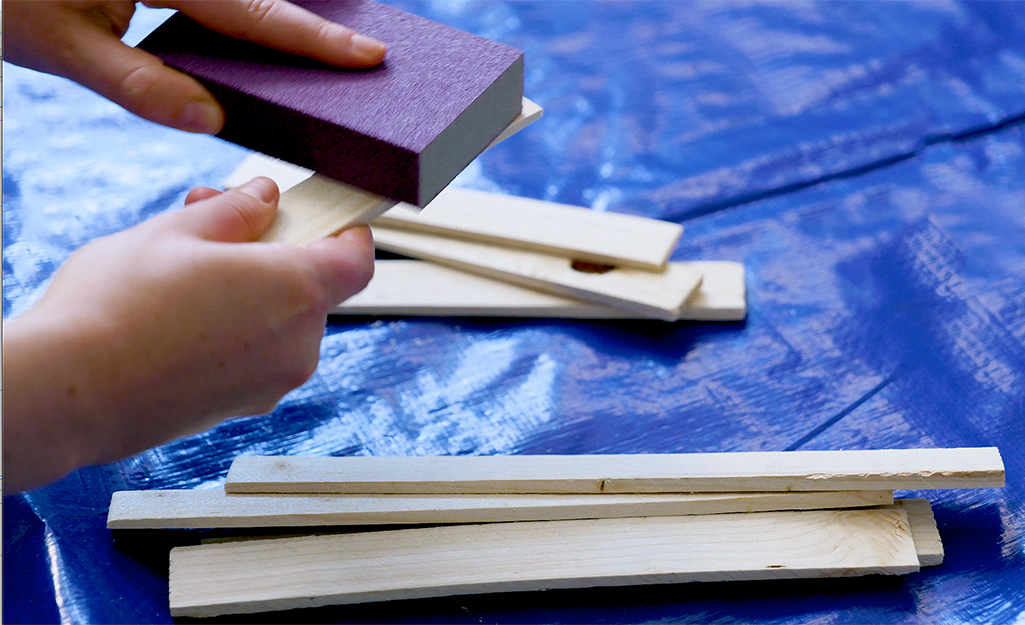 A person sands shims to remove any rough edges.