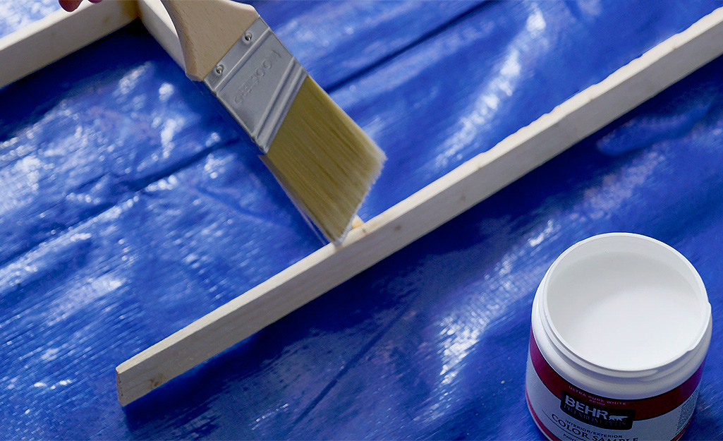 A person paints wood shims with white paint.