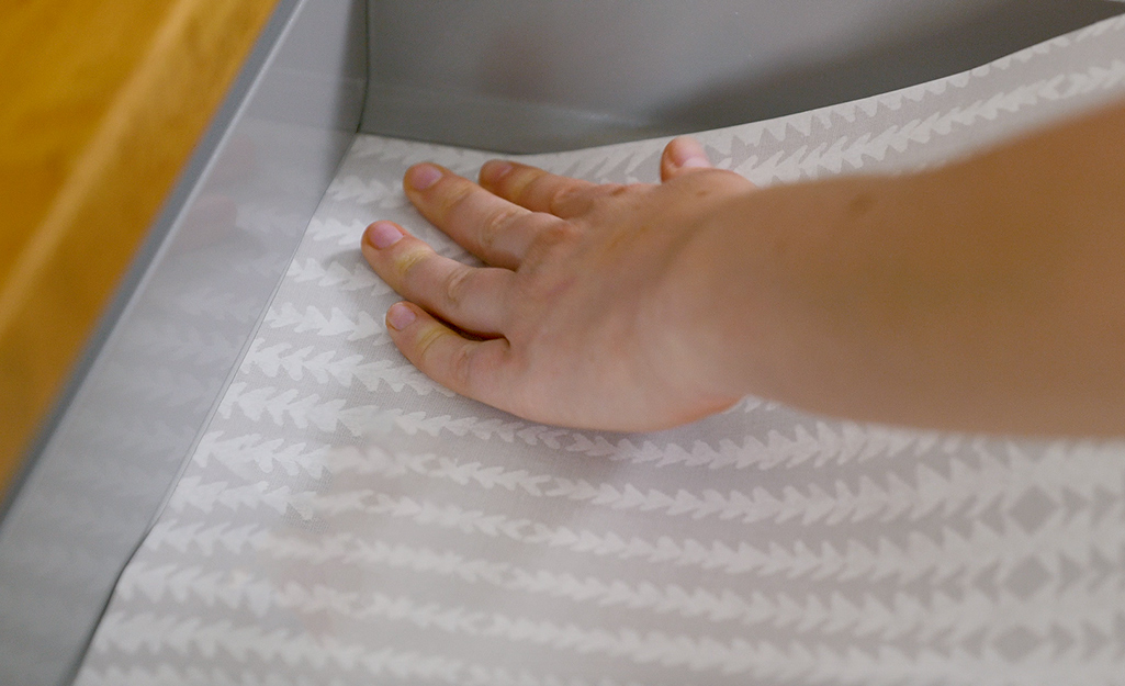 A person uses peel and stick wallpaper to line a drawer.