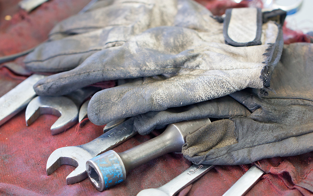 Work gloves and automotive tools laying on workbench.
