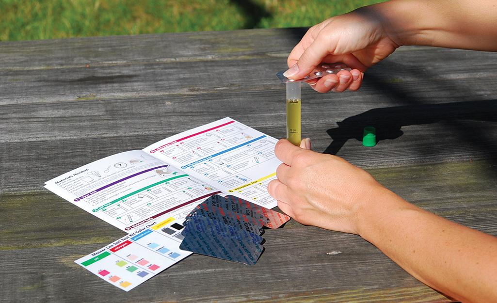 Person using a soil test kit.