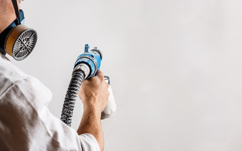 A person using a paint sprayer to apply wall paint texture.