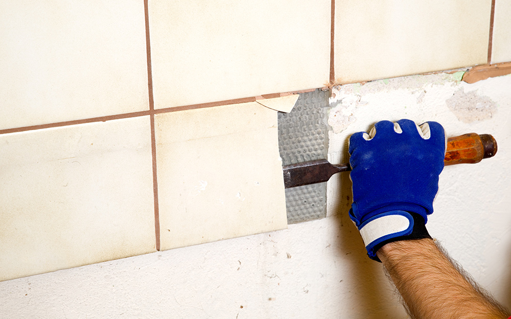 A person removing old tile from a shower wall.