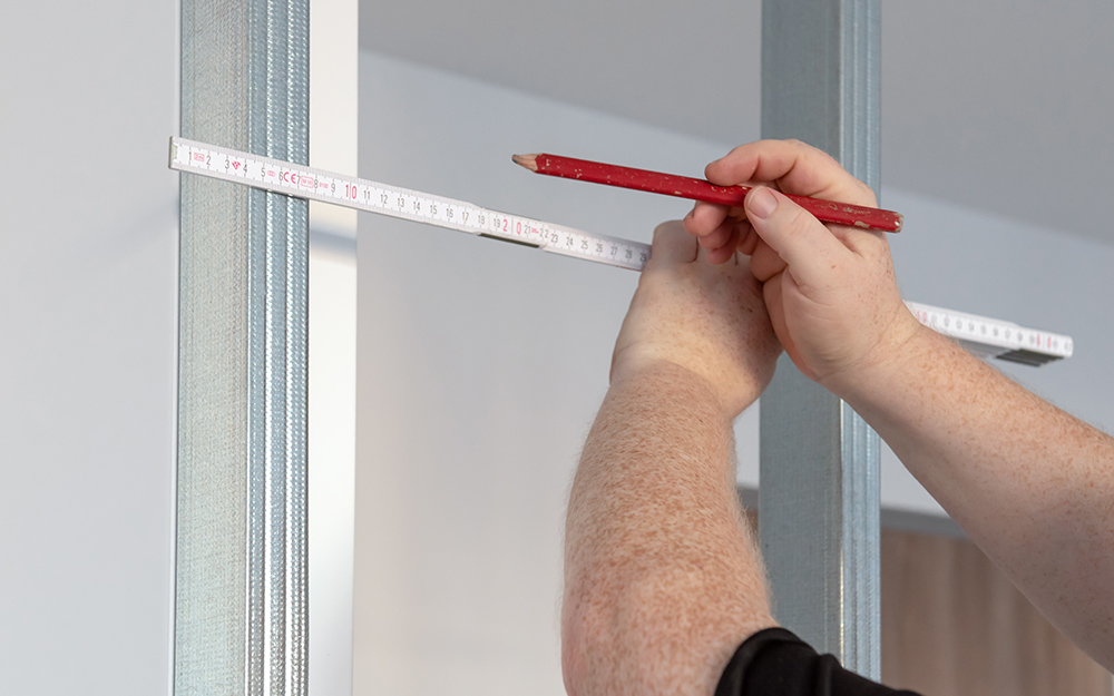 A person measuring a shower stall.