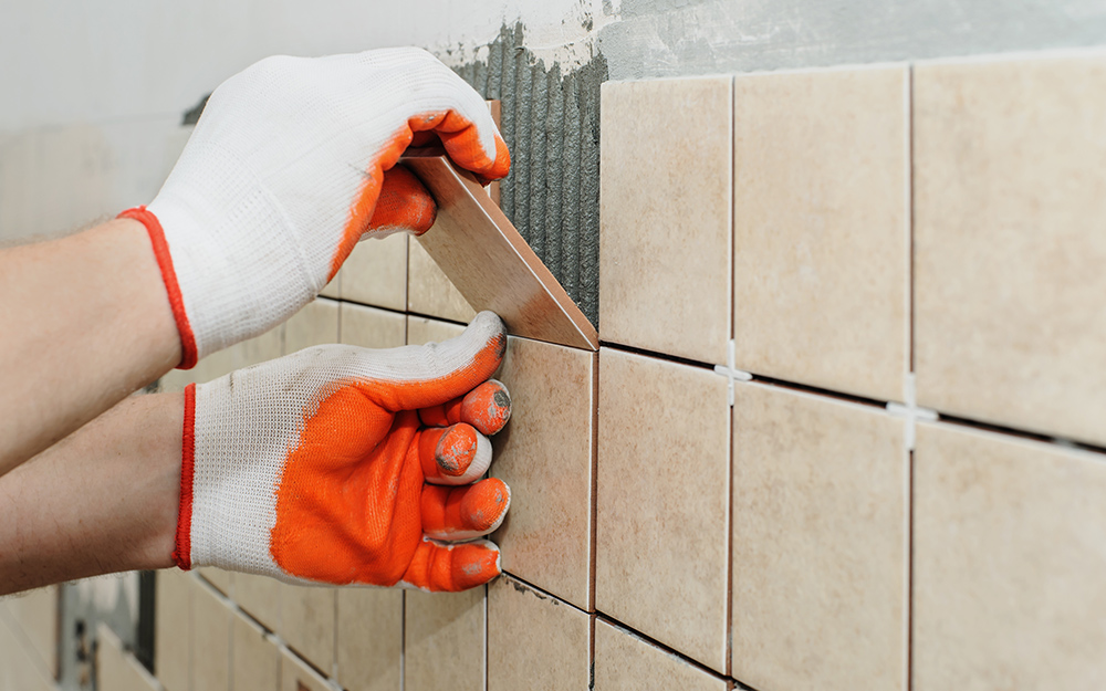 A person completing a tile row in a shower.