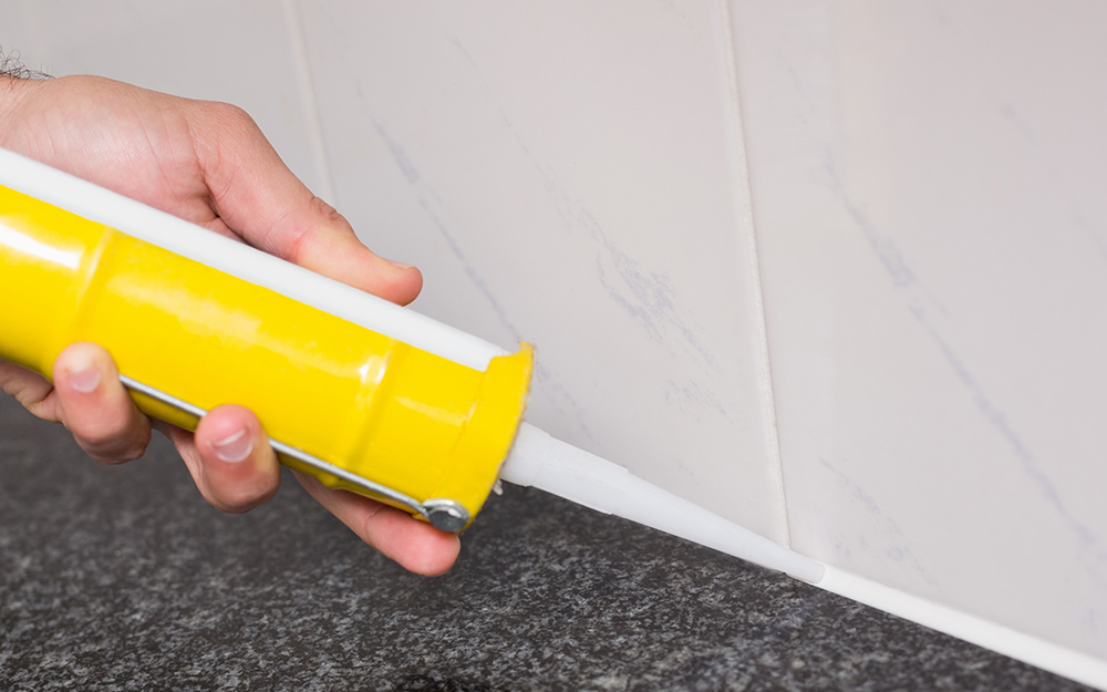 A person applying grout for shower tile installation.