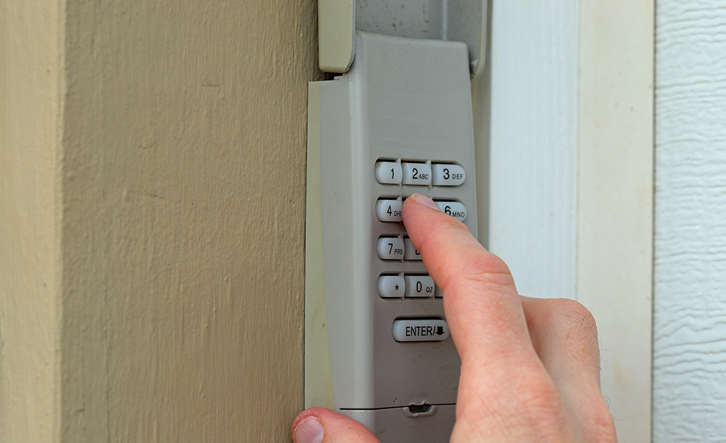 A person enters the code on a garage door opener keypad.