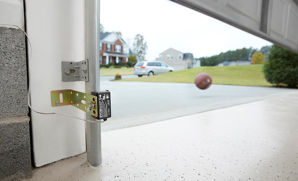A garage door safety sensor is attached to the side of a garage wall.