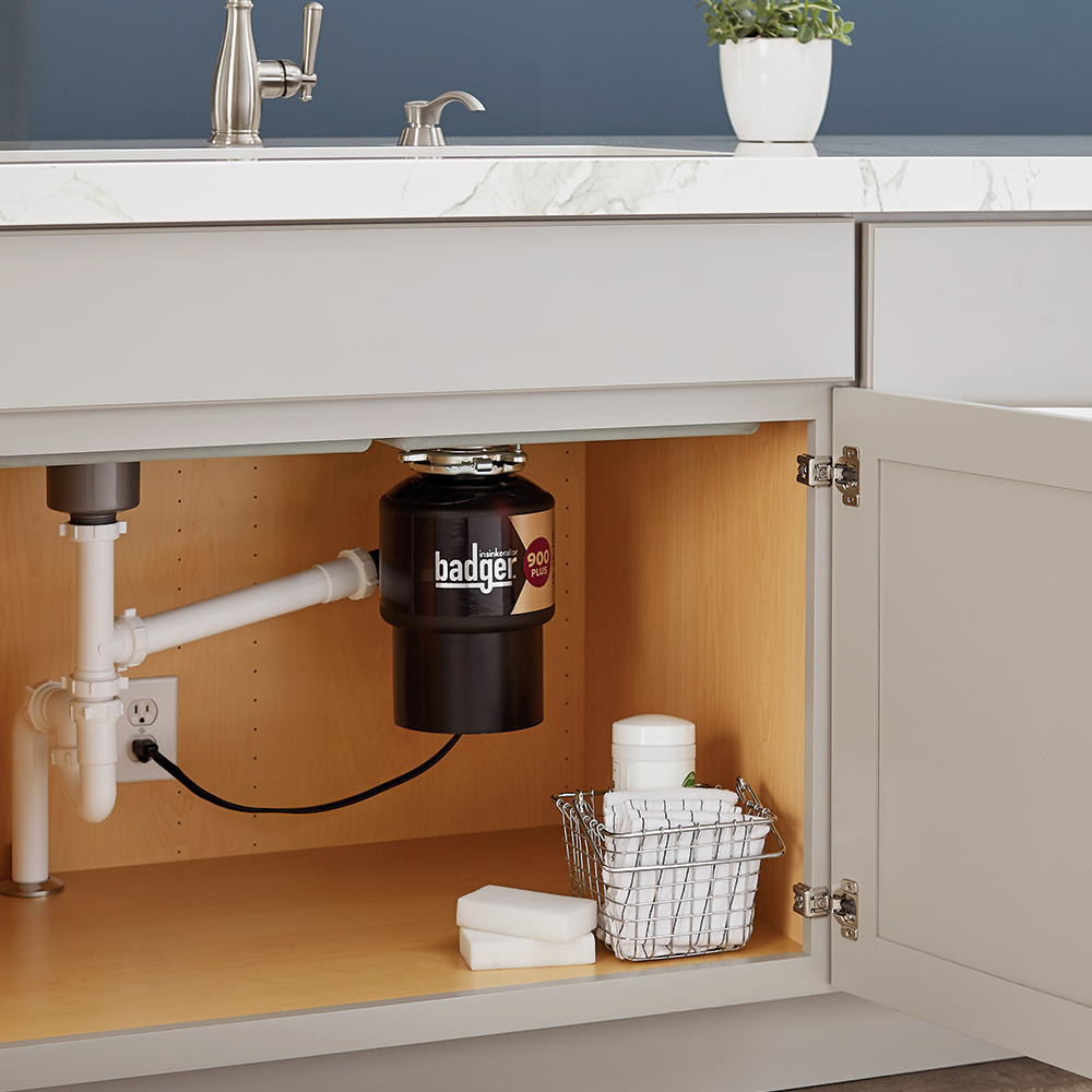 A cabinet under a kitchen sink stands open, showing pipes, a garbage disposal and a basket with towels and cleaning supplies.