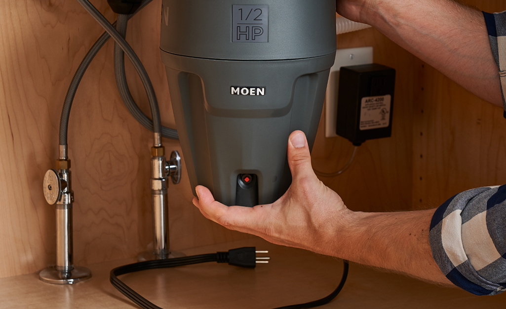 A person holds the top and bottom of a garbage disposal unit, which is unplugged inside a kitchen cabinet under a sink.