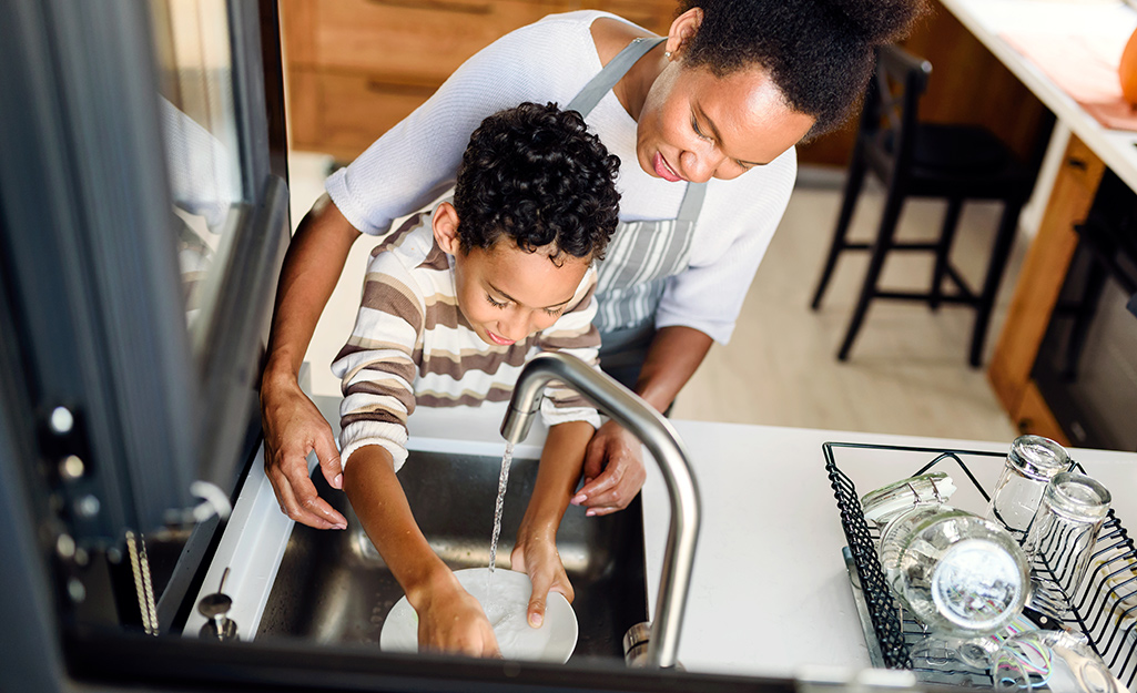 A woman in an apron stands behind a child and helps him as he rinses a plate off in a small kitchen sink by an open window.