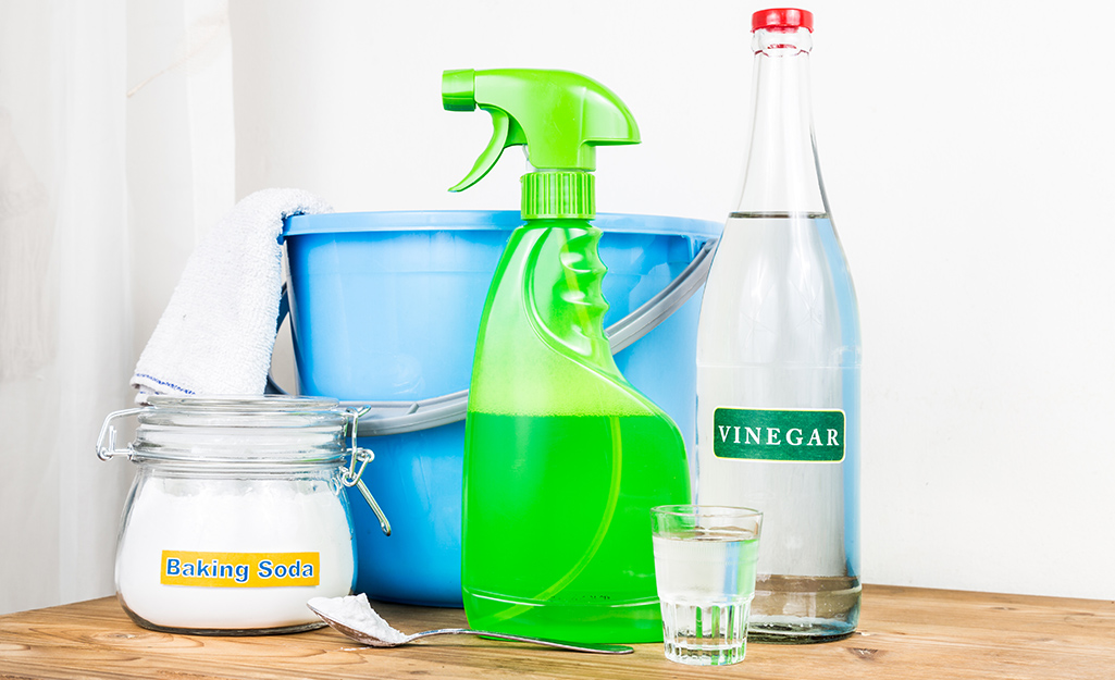 A bucket with a towel hung over the side, a bottle of vinegar, a glass and a container of baking soda and a spray bottle ready to use to unclog a shower drain.