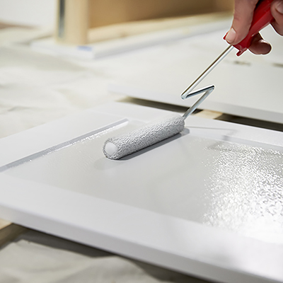 A person painting a cabinet white with a paint roller.