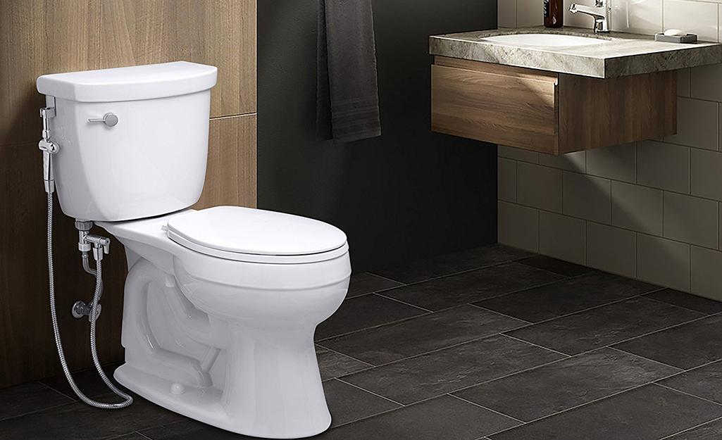 Một máy phun rửa vệ sinh cầm tay được lắp đặt bên cạnh bồn cầu trong phòng tắm.