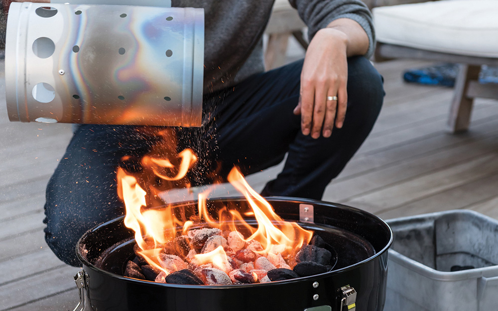 Person holding a charcoal chimney above a grill.