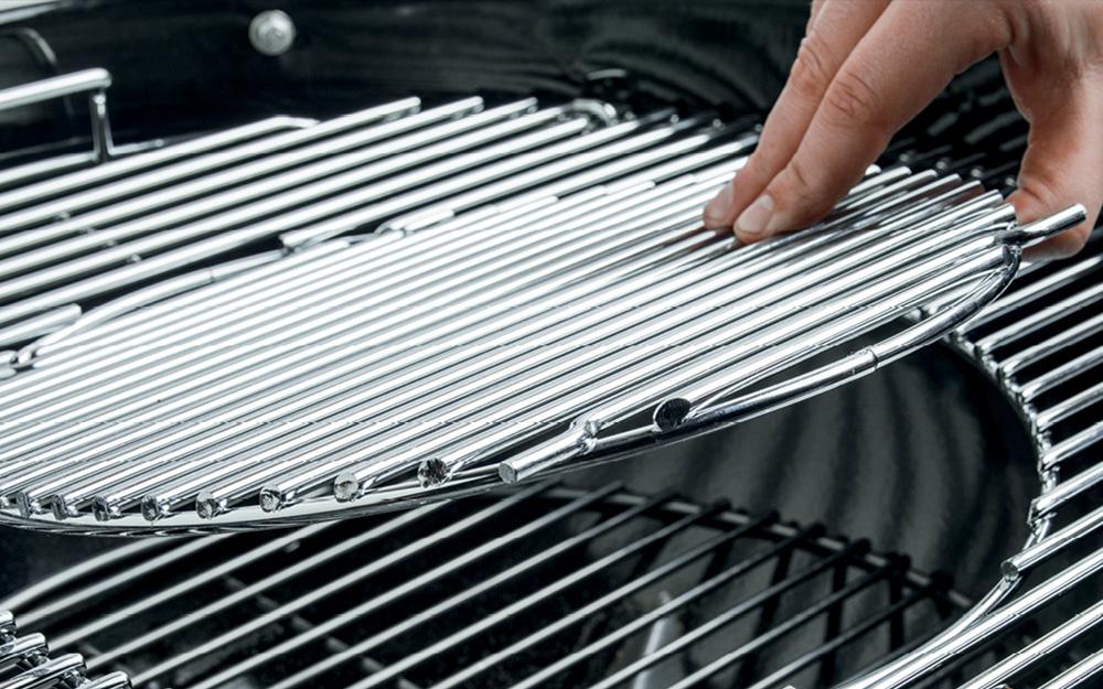 Person removes grill grates.