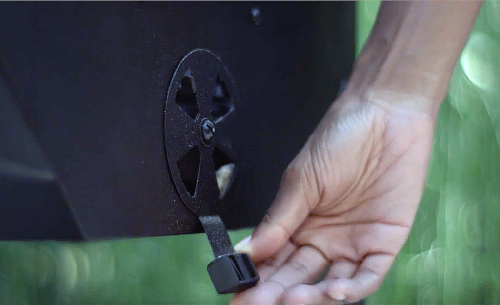 A person adjusting the lower vent on a charcoal grill.