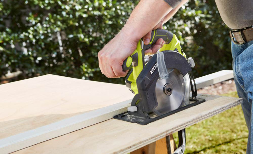 A circular saw being used to cut a straight line.