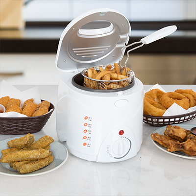 A white countertop deep fryer with a basket full of French fries.