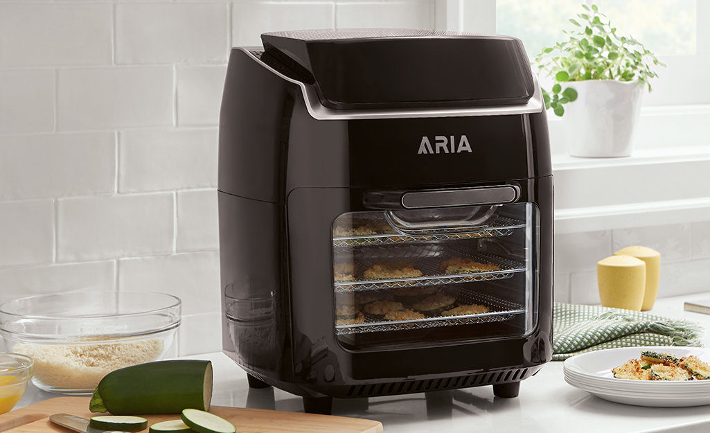 A black dehydrator on a kitchen counter in front of a window.