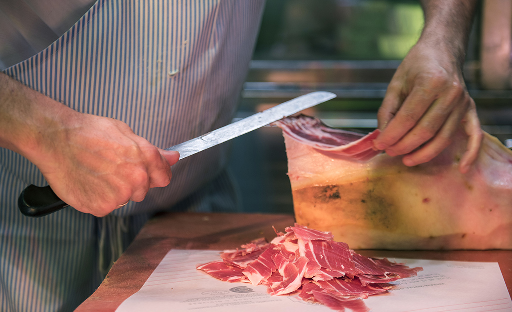 Man cutting thin slices of ham with a knife.