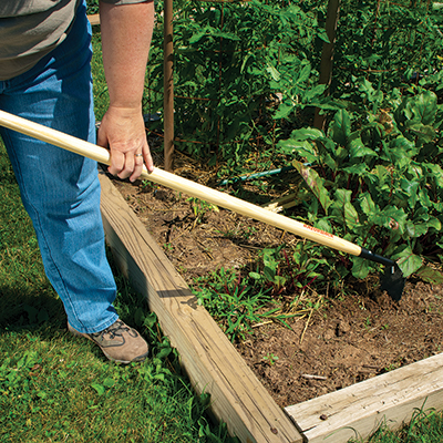 A person hoeing a garden bed.