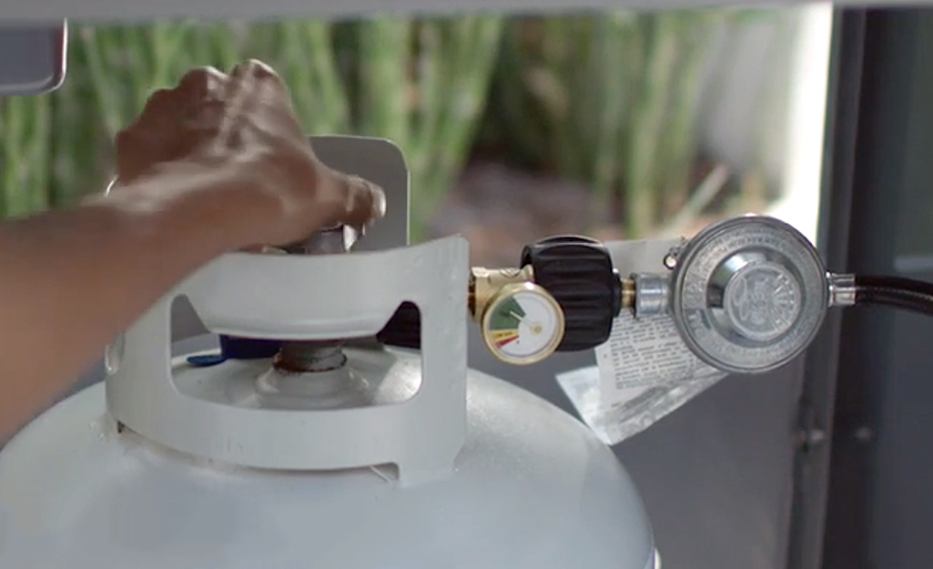 A person adjusting the valve on a propane tank.