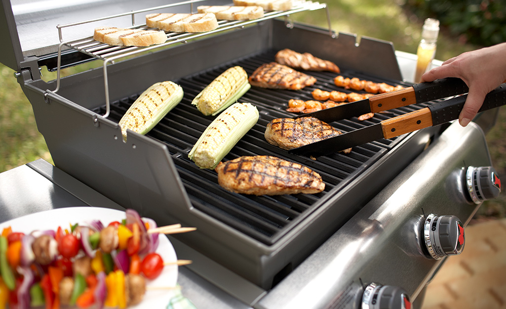 A person tending to a variety of food cooking on a gas grill.