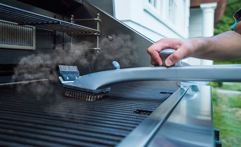 A person using a wire grill brush to clean a cooking grate.