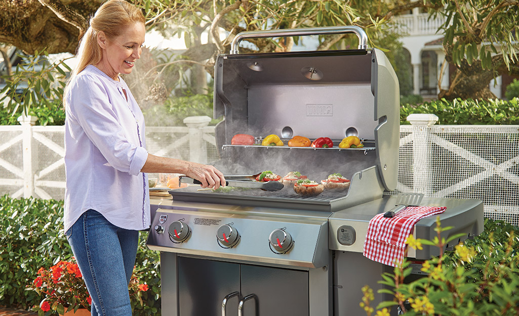 A person tending to food cooking on a gas grill.