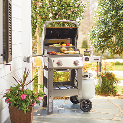 Food cooking on a gas grill on a patio.