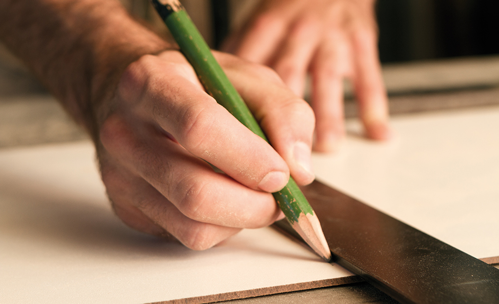 A person using a pencil and straight edge to mark a cutting line on a board.