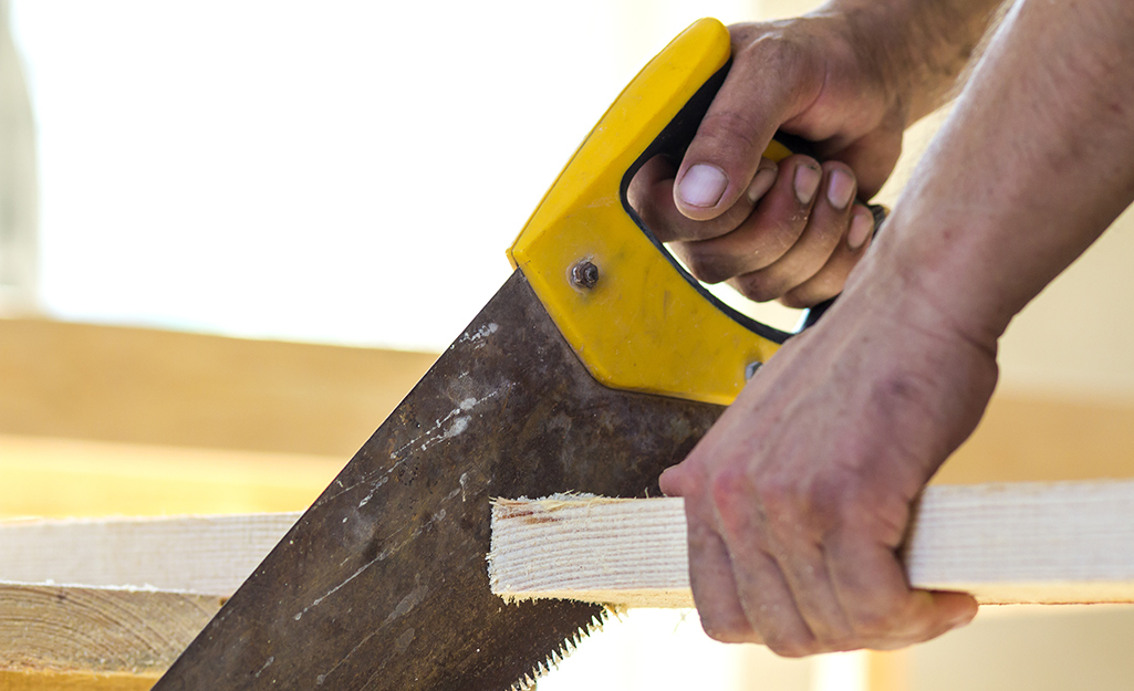 A person using a hand saw to cut a board.