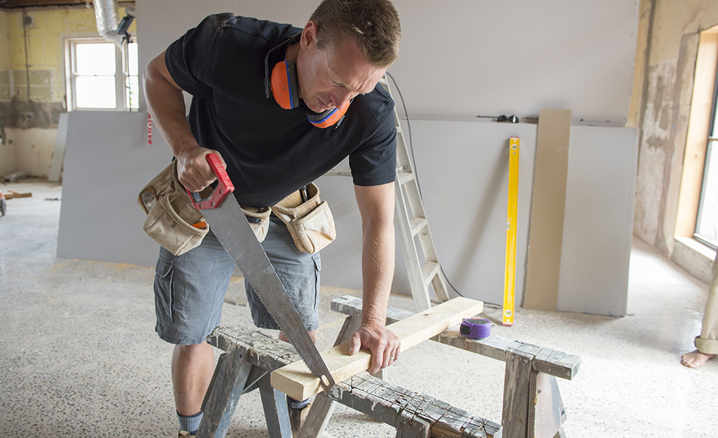 A person using a hand saw to cut a board that is braced on saw horses.