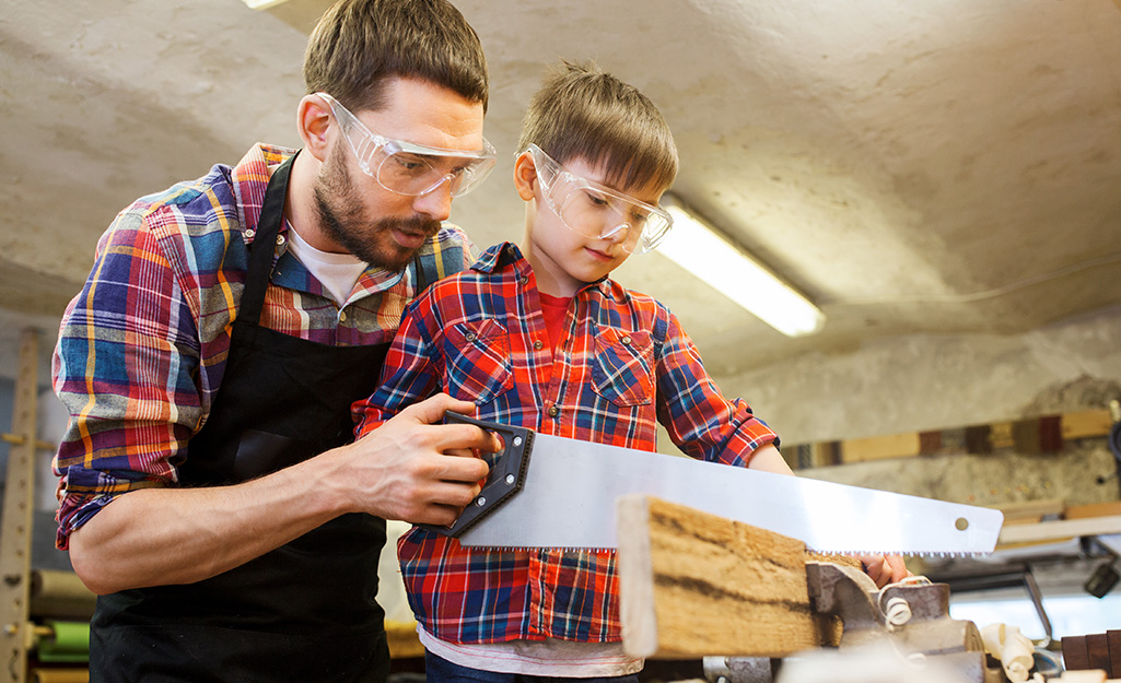 An adult helping a child use a hand saw to cut a board.