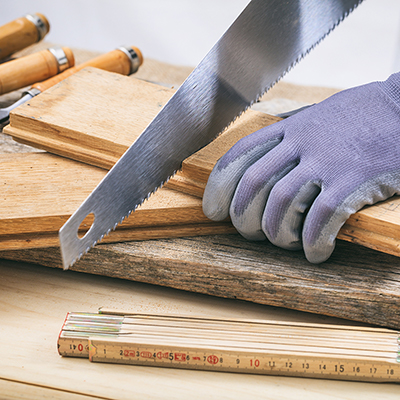 A person holding a board while using a hand saw to cut it.