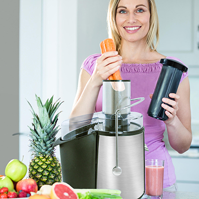 A woman adds carrots to a juicer.