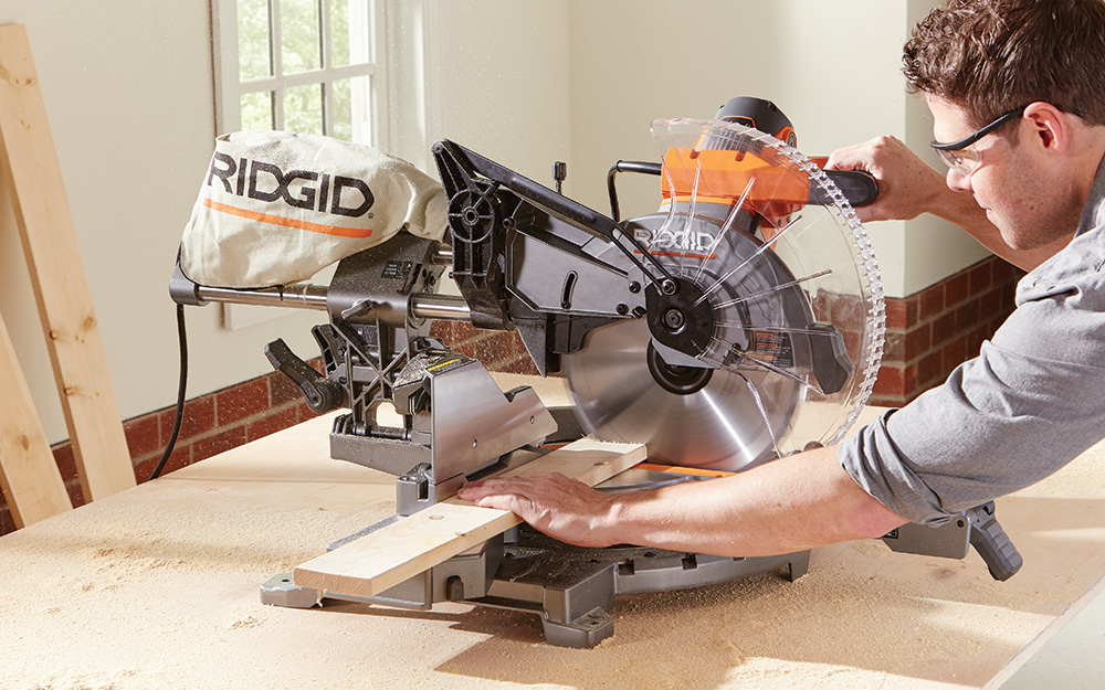 A person braces a board on a miter saw with one hand as he pushes the saw handle forward to make the cut.