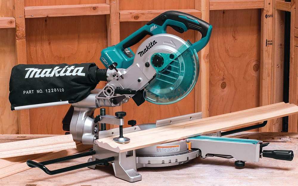 The arm of a miter saw is positioned at an angle to make a miter cut.