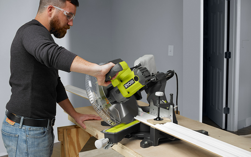 A miter saw is tilted at an angle to make a bevel cut on a board.