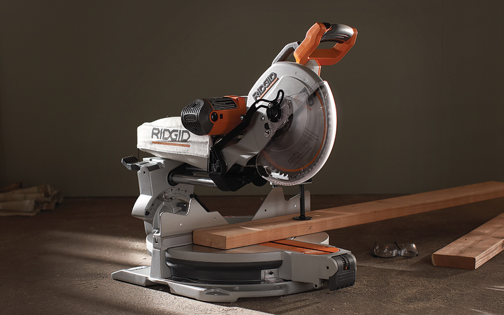 A power miter saw has a board on its base ready to be cut.