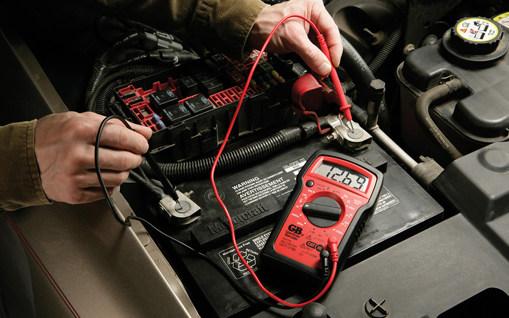 Someone using a multimeter on an engine