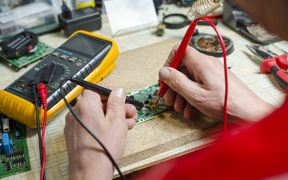 Someone using a multimeter to measure resistance