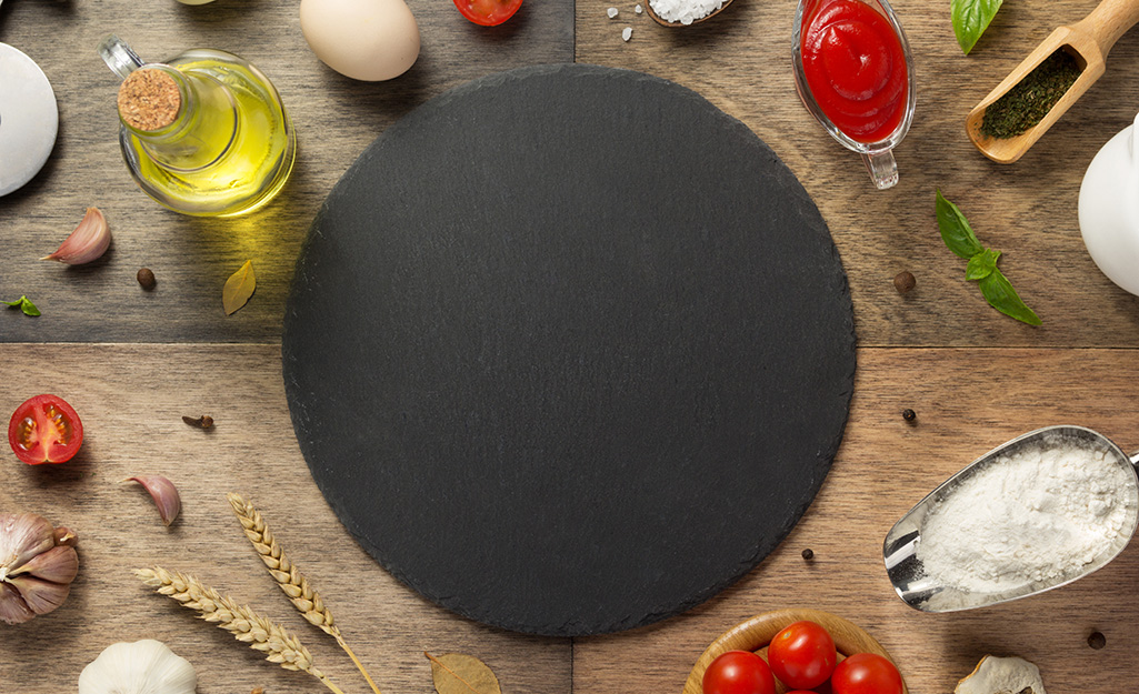 Empty black pizza stone surrounded by pizza ingredients