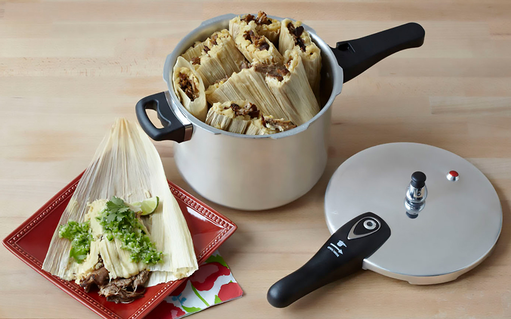 Cooked tamales stand on a plate and inside a pressure cooker.